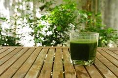 在木桌上的一块绿色汁液玻璃在庭院里 免版税库存图片