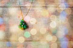在木桌上的一点圣诞树垂饰,与五颜六色的bokeh 库存图片
