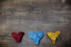 在木桌上的三张五颜六色的心形的被弄皱的纸 华伦泰` s 恋人` s天 2月14日概念 库存照片