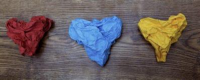 在木桌上的三张五颜六色的心形的被弄皱的纸 华伦泰` s 恋人` s天 2月14日概念 免版税图库摄影