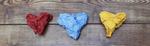 在木桌上的三张五颜六色的心形的被弄皱的纸 华伦泰` s 恋人` s天 2月14日概念 图库摄影
