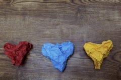 在木桌上的三张五颜六色的心形的被弄皱的纸 华伦泰` s 恋人` s天 2月14日概念 库存图片