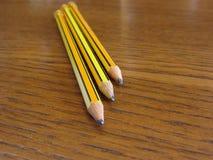 在木桌上的三支使用的铅笔 库存照片
