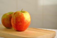 在木桌上的两个红色新鲜的苹果 库存图片