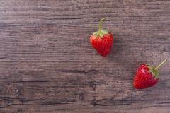 在木桌上的两个红色草莓 库存图片