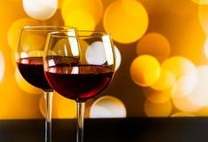 在木桌上的两块红葡萄酒玻璃反对金黄bokeh点燃背景 库存照片