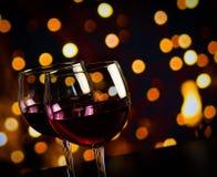 在木桌上的两块红葡萄酒玻璃反对bokeh点燃背景 免版税库存图片