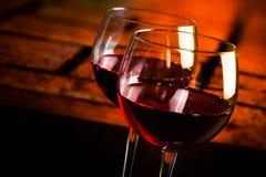 在木桌上的两块红葡萄酒玻璃有温暖的大气背景 免版税库存照片