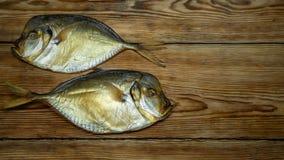 在木桌上的两条熏制的鱼 库存照片