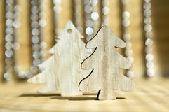 在木桌上的两棵木圣诞树,在背景的反射,圣诞节链子 免版税库存照片