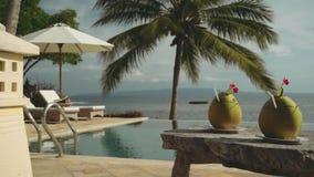 在木桌上的两份椰子饮料在无限游泳池和海洋前面 股票录像