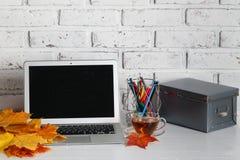 在木桌上的个人便携式计算机在砖墙背景 库存照片