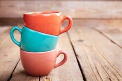 在木桌上的五颜六色的咖啡杯在难看的东西背景 免版税库存照片