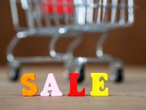 在木桌上的五颜六色的木木词销售和购物车和的背景 英语字母表由木信件颜色制成 库存照片