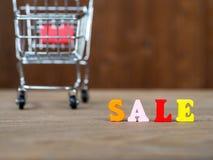 在木桌上的五颜六色的木木词销售和购物车和的背景 英语字母表由木信件颜色制成 免版税库存照片
