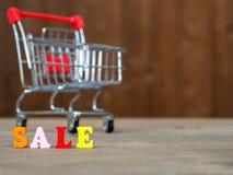 在木桌上的五颜六色的木木词销售和购物车和的背景 英语字母表由木信件颜色制成 图库摄影