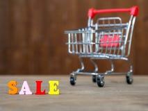 在木桌上的五颜六色的木木词销售和购物车和的背景 英语字母表由木信件颜色制成 T 库存照片