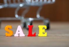 在木桌上的五颜六色的木木词销售和购物车和的背景 英语字母表由木信件颜色制成 T 图库摄影