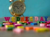 在木桌上的五颜六色的木词星期三和葡萄酒闹钟和背景是浅灰蓝色 英语字母表被做求爱 库存图片