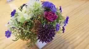 在木桌上的五颜六色的玫瑰花束 免版税库存图片