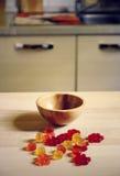 在木桌上的五颜六色的胶粘的熊糖果在厨房背景 库存照片