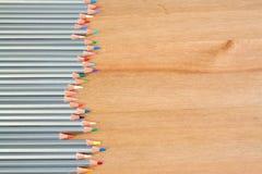 在木桌上的五颜六色的铅笔 平的位置样式 库存图片