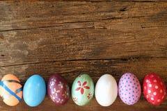 在木桌上的五颜六色的食者鸡蛋 背景上色了复活节彩蛋eps8格式红色郁金香向量 复制空间 免版税图库摄影