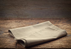 在木桌上的亚麻布餐巾 免版税库存照片