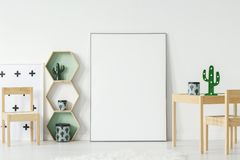 在木桌上的仙人掌在与大模型的白色空的海报旁边 免版税库存图片