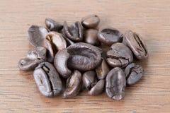 在木桌上的低质量不好咖啡豆 免版税库存图片