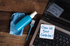 在木桌上的便携式计算机与笔记清扫您的计算机 库存照片