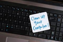 在木桌上的便携式计算机与笔记清扫您的计算机 库存图片