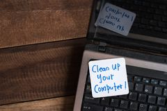 在木桌上的便携式计算机与笔记清扫您的计算机 免版税库存图片