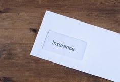 在木桌上的信件 与保险索赔的纸信封 免版税库存图片