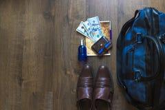 在木桌上的假日手提箱与美元多金钱 免版税库存照片