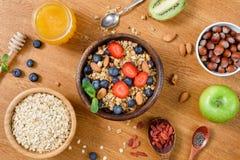 在木桌上的健康滋补早餐:燕麦、格兰诺拉麦片、果子、蜂蜜和超级食物 库存照片