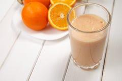 在木桌上的健康饮料桔子和香蕉圆滑的人 库存照片