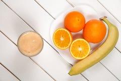 在木桌上的健康饮料桔子和香蕉圆滑的人 库存图片
