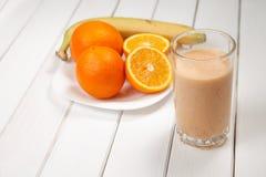 在木桌上的健康饮料桔子和香蕉圆滑的人 免版税库存图片