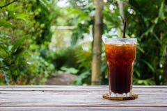 在木桌上的冰冻咖啡有绿色自然背景 复制空间 库存照片