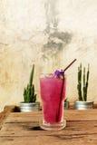 在木桌上的凉快的蝴蝶豌豆汁由在铝罐和概略的水泥墙壁背景的仙人掌装饰 免版税库存照片