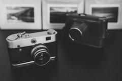 在木桌上的减速火箭的葡萄酒照相机和照片框架 免版税库存照片