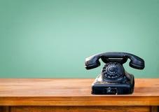 在木桌上的减速火箭的黑电话 免版税库存图片