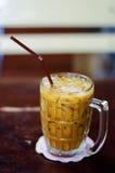 在木桌上的刷新的被冰的咖啡拿铁在餐馆和c 免版税库存照片