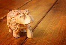 在木桌上的印地安小雕象大象 库存照片