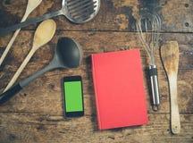 在木桌上的厨房器物与书和巧妙的电话 免版税库存照片