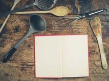 在木桌上的厨房器物与书 免版税库存照片