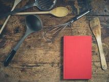 在木桌上的厨房器物与书 库存照片