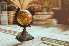 在木桌上的古色古香的地球模型与橙色阳光,葡萄酒样式 免版税库存照片
