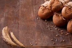 在木桌上的另外面包,麦子,纸袋,绳索,麦子的耳朵 库存照片